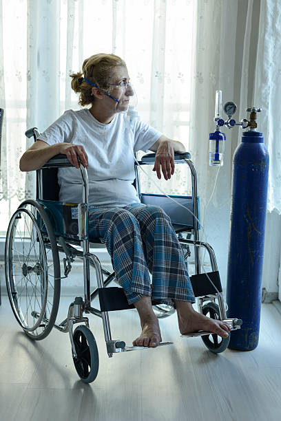 Woman In Wheelchair With Oxygen Mask Senior Woman In Wheelchair With Oxygen Mask. oxygen tube stock pictures, royalty-free photos & images