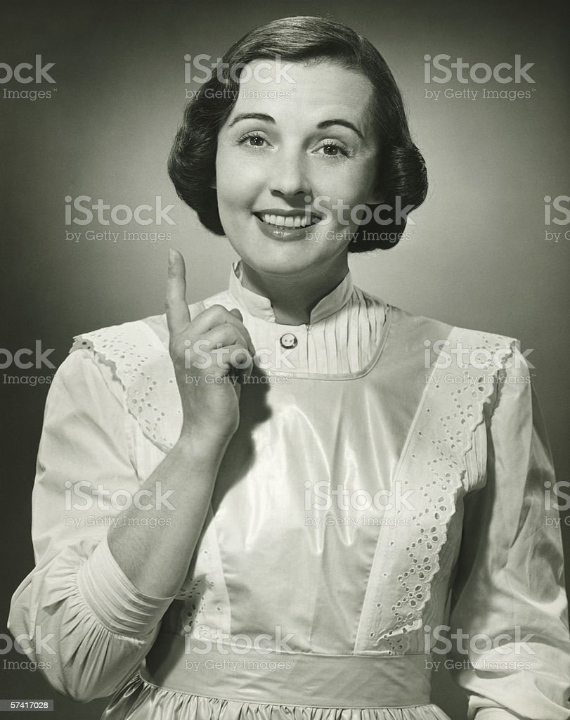 Woman in white apron pointing with finger in studio, (B&W), (Portrait) stock photo
