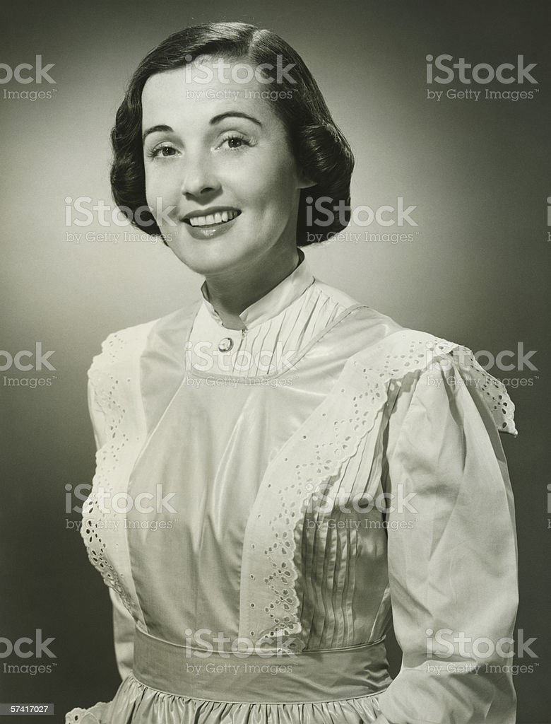 Woman in white apron posing in studio, (B&W), (Portrait) stock photo