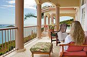 blond hair woman in a white bathrobe reading a book on a patio of a luxury Caribbean villa