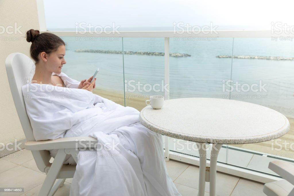 Mujer De Manto Blanco Con Teléfono Inteligente En Casa