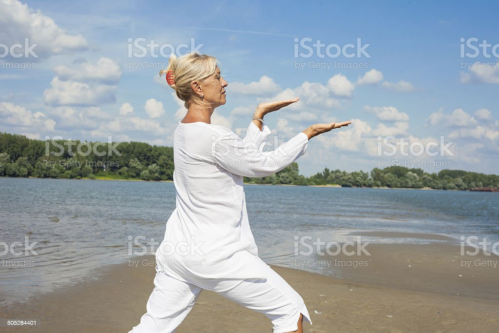 Woman in white clothes doing tai chi stock photo