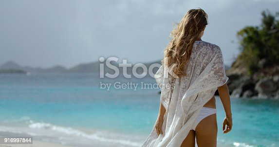 attractive blonde woman in white cover up on tropical beach in the Caribbean, St John, united states virgin islands