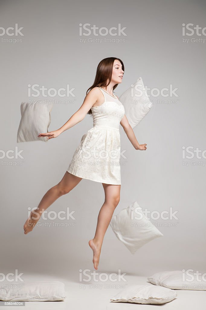 Woman in white dress in mid air with flying pillows - Photo