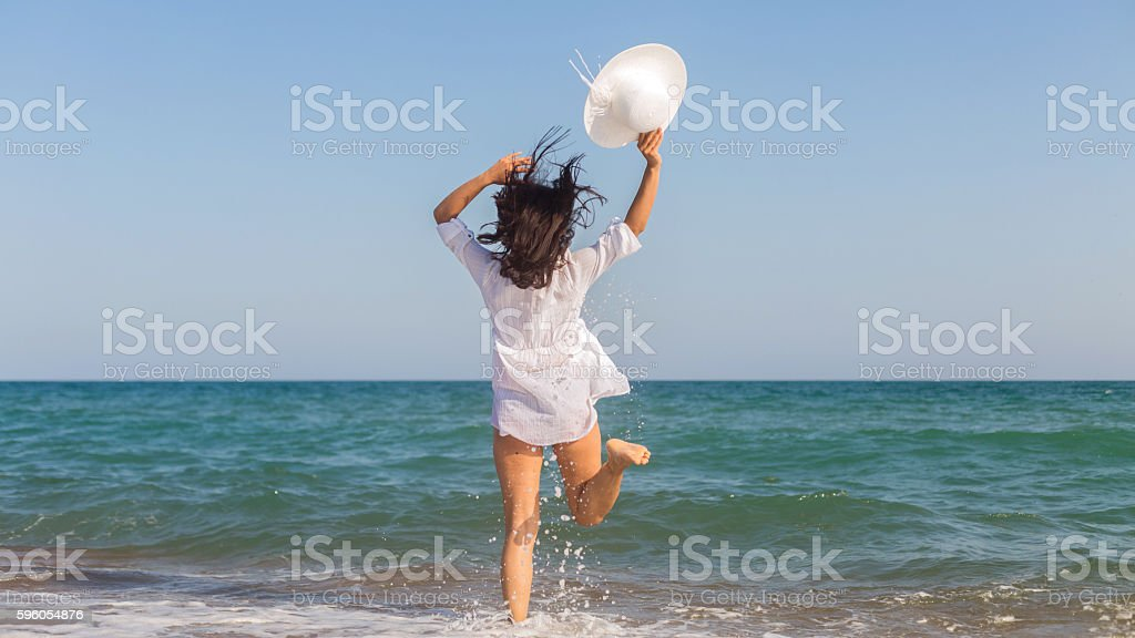 Woman in white dress jumping on the beach. royalty-free stock photo