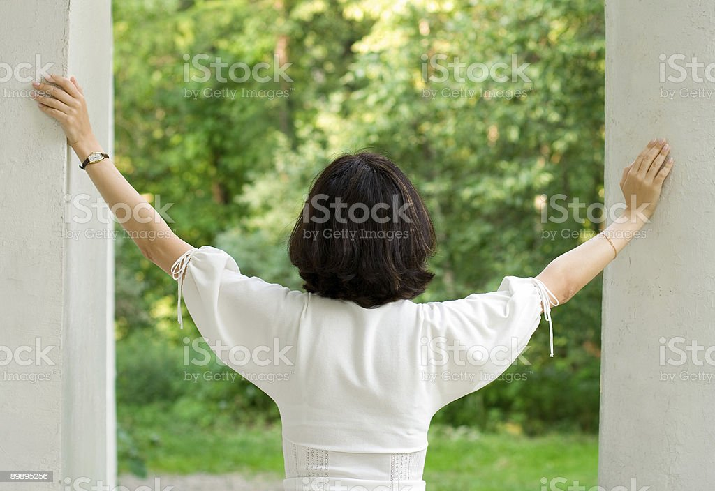 Mujer en vestido blanco mirando por la ventana foto de stock libre de derechos