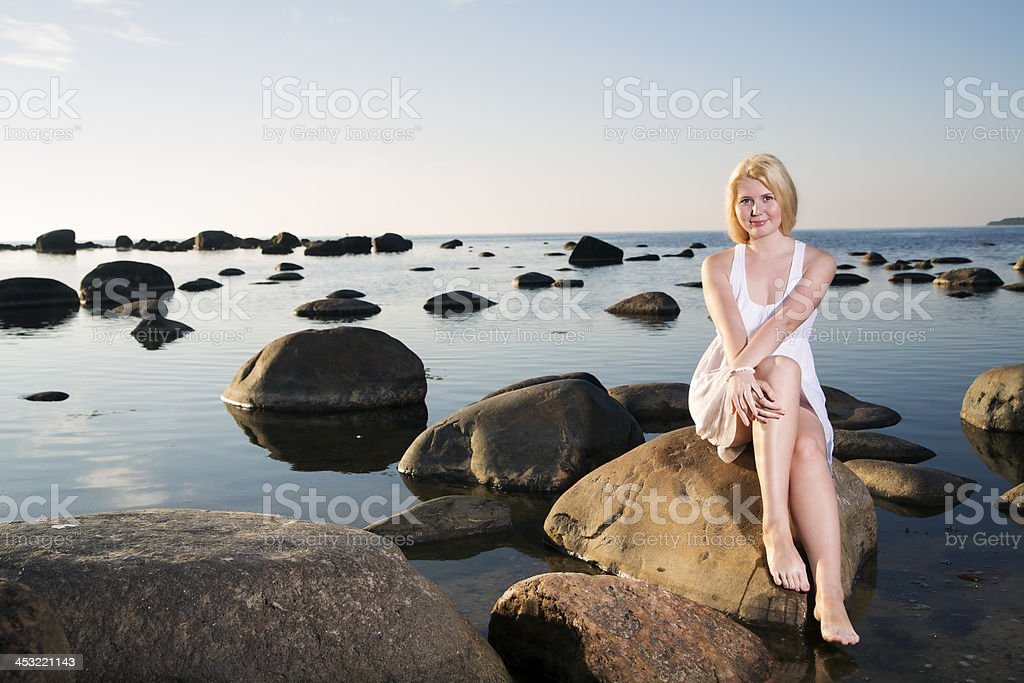 Woman in white dress sit on stone royalty-free stock photo