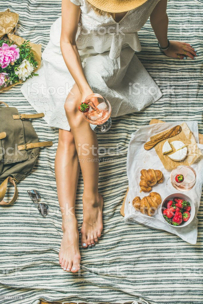 Woman in white dress sitting with wine and snacks stock photo