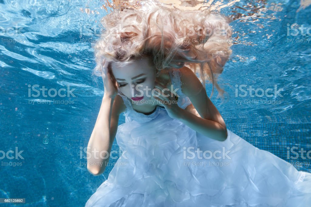 Woman in white dress under water pool. stock photo
