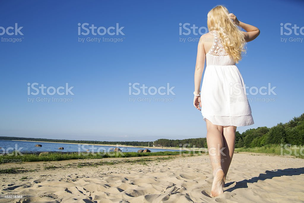 Woman in white dress walking at beach royalty-free stock photo