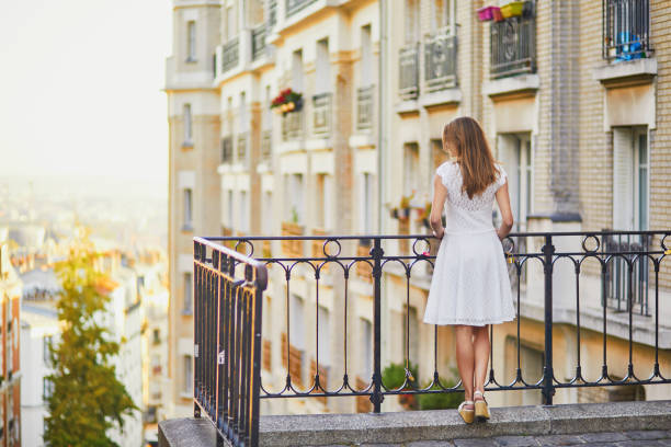 woman in white dress walking on famous Montmartre hill in Paris stock photo
