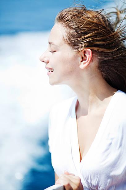 frau im weißen kleid wind weht in ihr gesicht - haare ohne lockenstab wellen stock-fotos und bilder