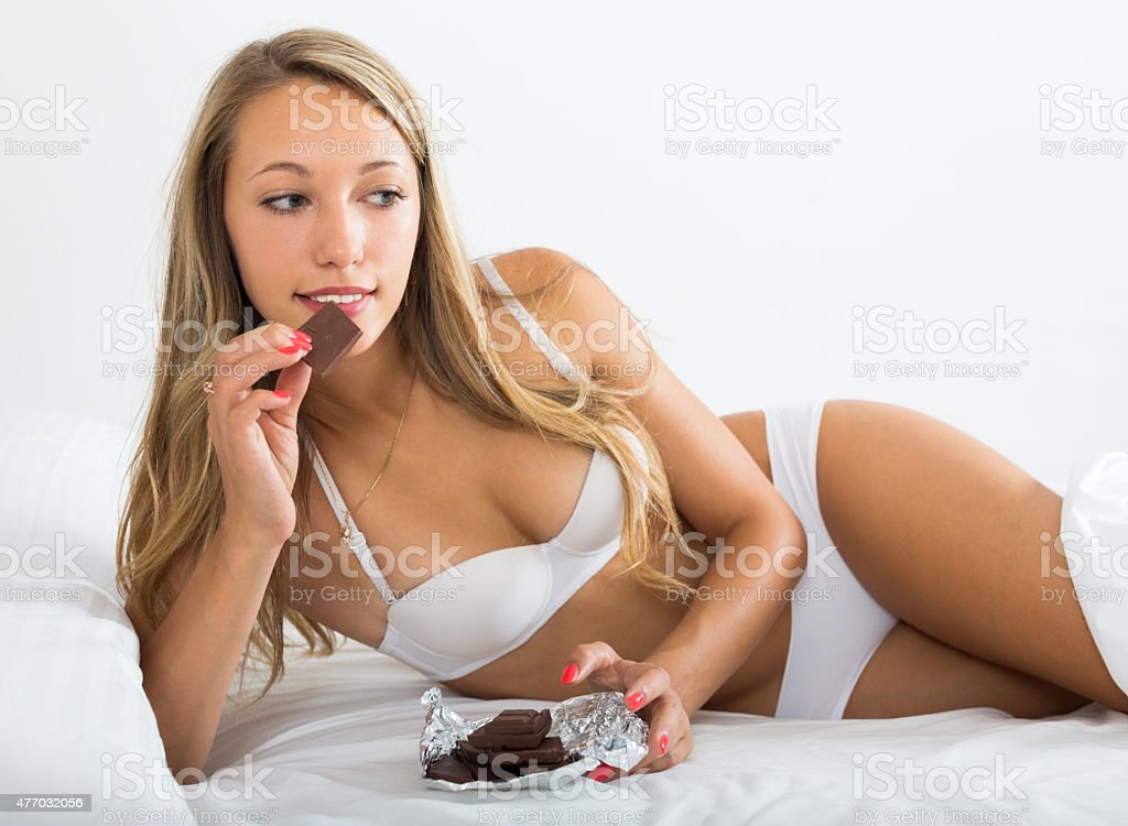 Woman in white eating chocolate in her bed stock photo