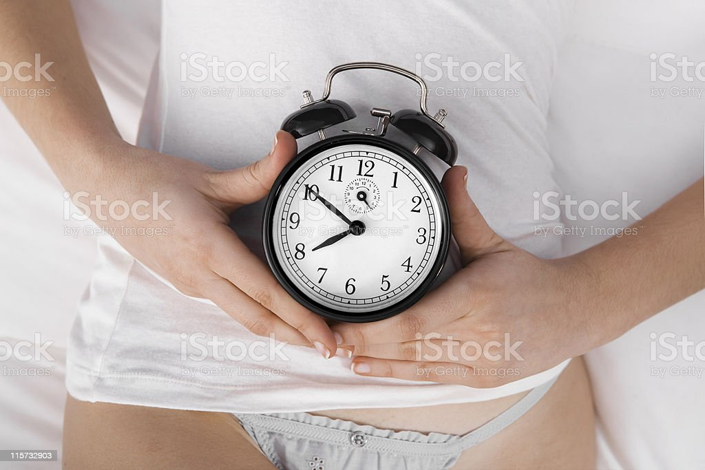 Woman in white holding a black clock over her abdomen stock photo