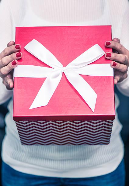 woman in white knitted sweater hold christmas gift - basteln mit zeitungspapier stock-fotos und bilder