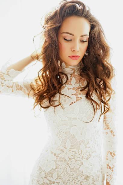 frau im weißen spitzenkleid mit gewellt lange haare - hochzeitskleid marken stock-fotos und bilder