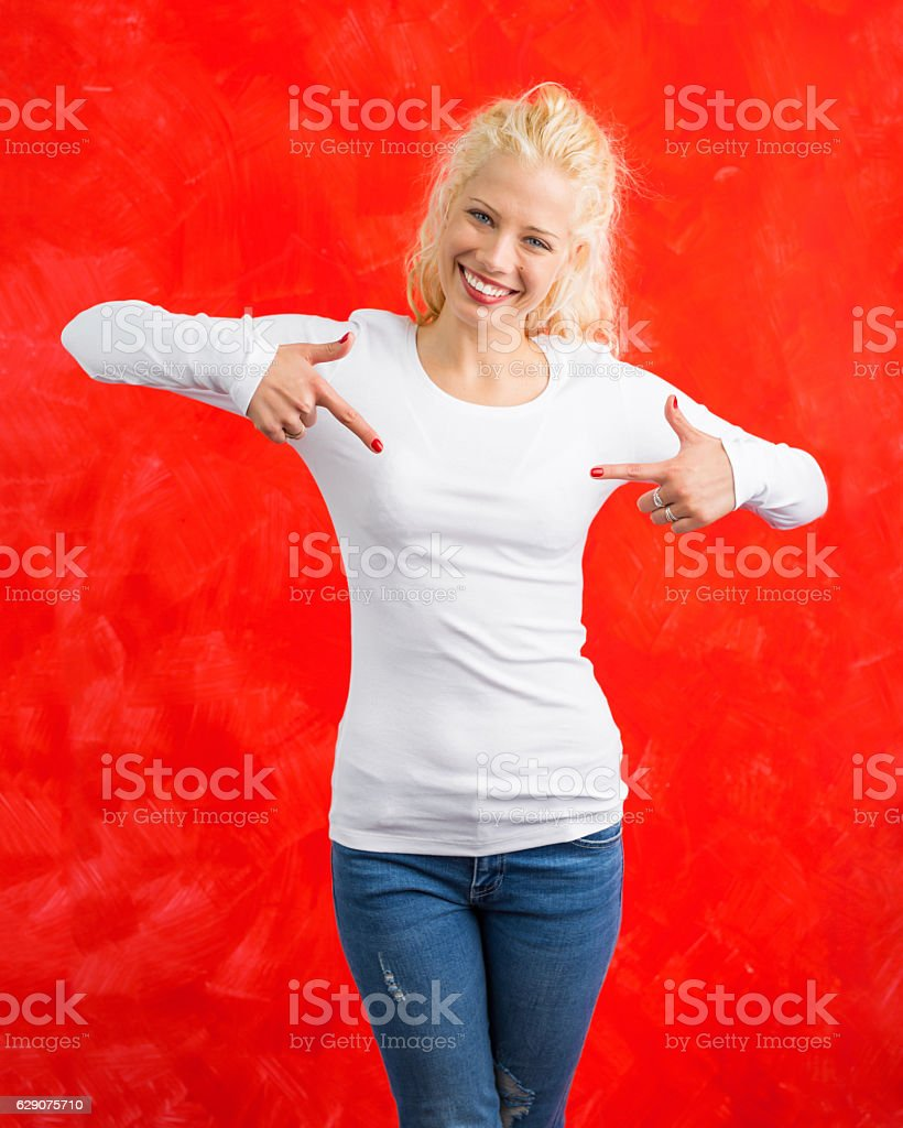 Woman in white long sleeve shirt on red background pointing stock photo