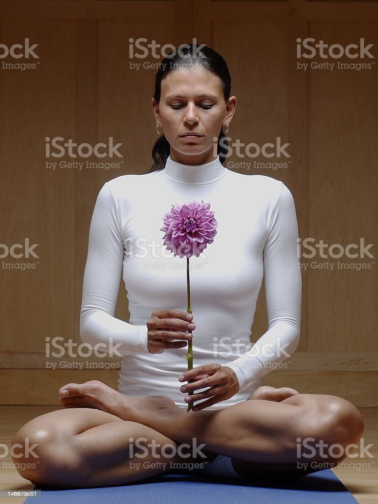 Woman in White Meditating and Holding Flower royalty-free stock photo