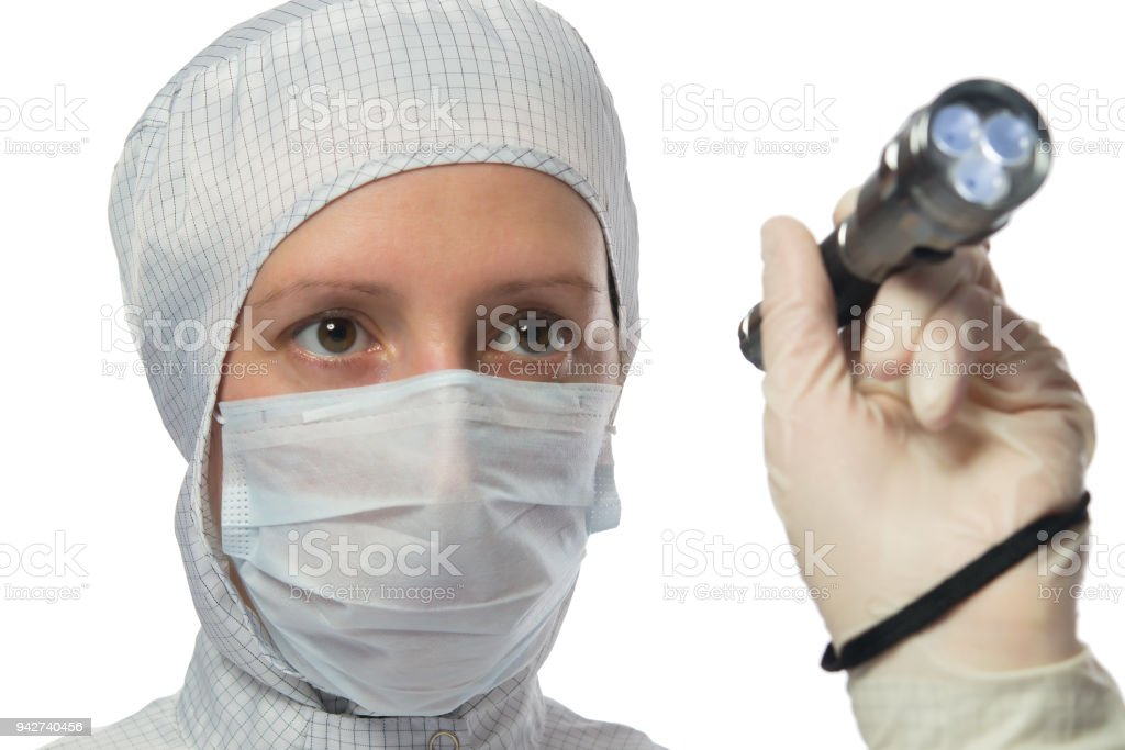 woman in white protective suit, studying and holding a flashlight in her hand, on white stock photo