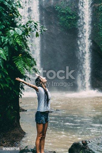 Mature Caucasian woman   in white shirt standing near  Tibumana   waterfall under the rain  in Bali, Indonesia