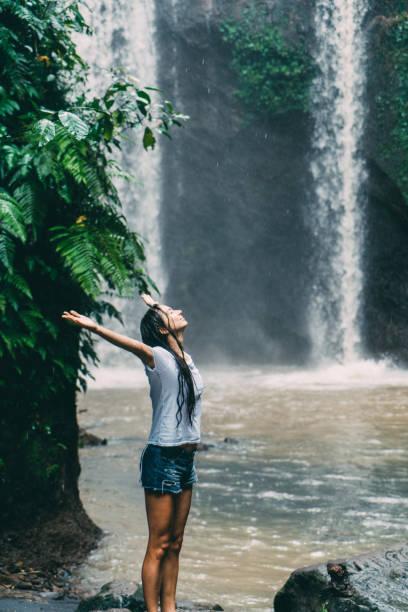 frau in weißem hemd stand in der nähe tibumana wasserfall unter dem regen in bali, indonesien - regenzeit stock-fotos und bilder