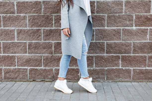 woman in white sneakers and blue jeans, gray coat near a brick wall - hair line surface stock photos and pictures