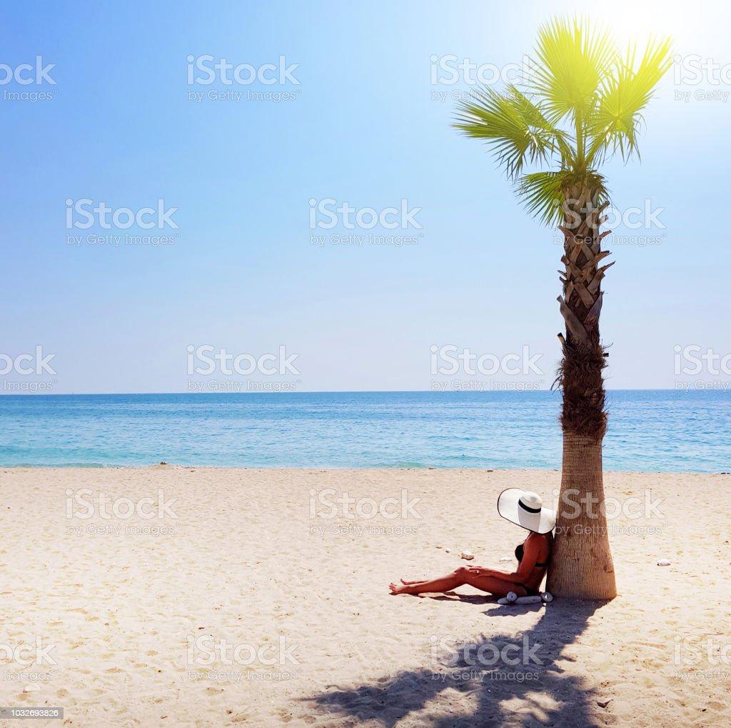75117c992783 Una Mujer De Sombrero De Paja Blanco Sentados Bajo La Palmera En La ...