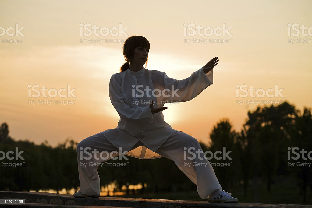 woman in white suit make's taiji chuan exercise - 4 stock photo