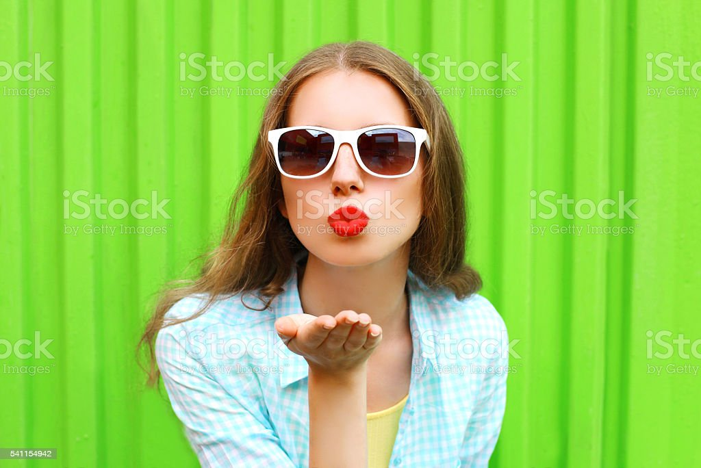 Woman in white sunglasses sends an air kiss over green stock photo