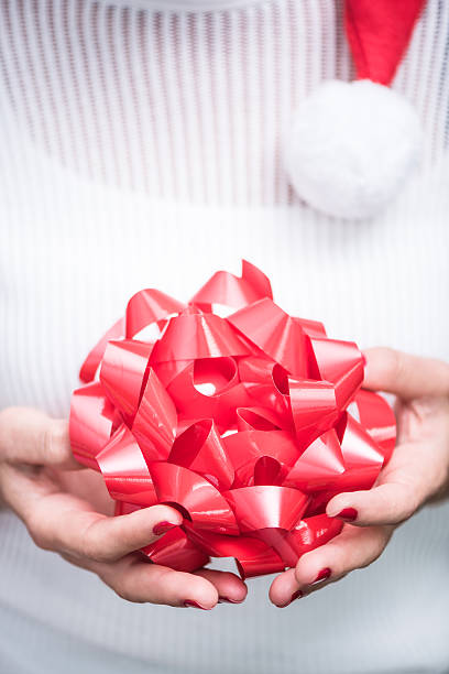 woman in white sweater hold red christmas ribbon - basteln mit zeitungspapier stock-fotos und bilder