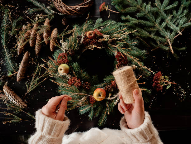 Woman in white sweater making a Christmas wreath stock photo