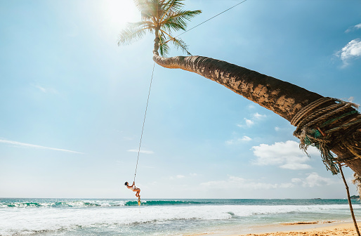 Woman in white swimsuit swinging on tropical palm swing over the ocean waves. Careful summer tropic climate countries vacation concept image.