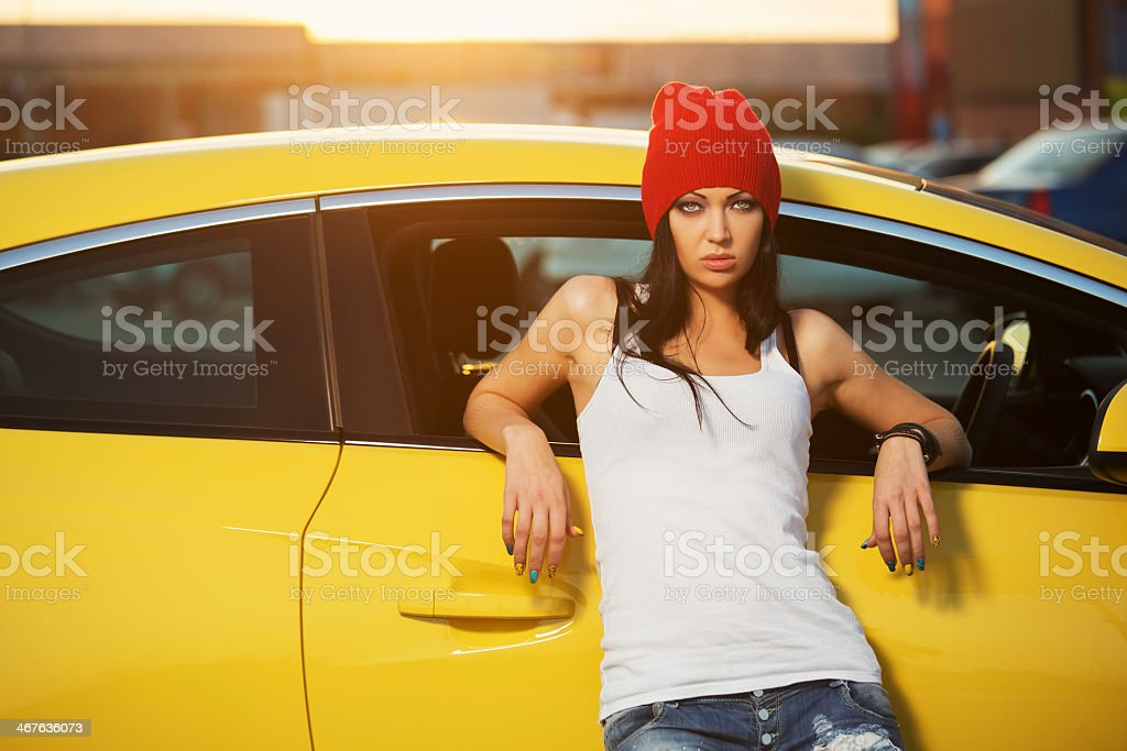 Woman in white tank top and red beanie leaning on yellow car stock photo