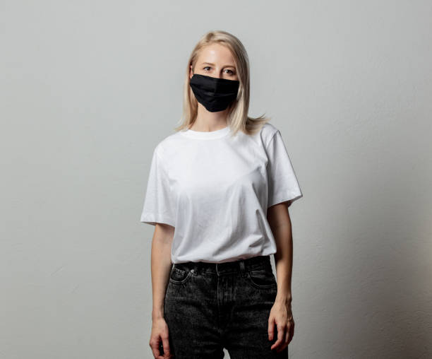 Woman in white t-shirt and black face mask on white background stock photo