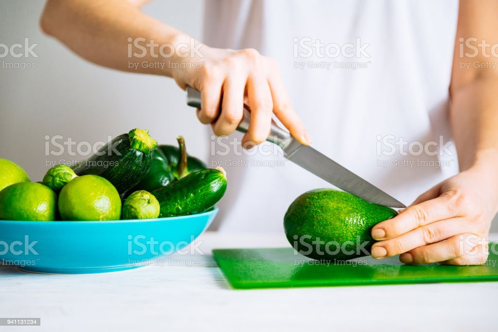 woman in white t-shirt cut avocado on green board. healthy food stock photo