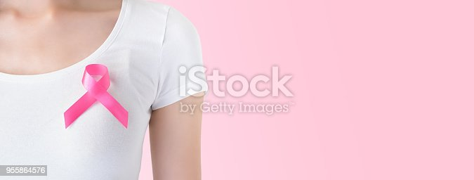 istock Woman in white t-shirt with pink ribbon on her chest, supporting symbol of breast cancer awareness campaign in October 955864576