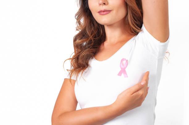 mulher de camiseta branca com fita rosa apoiando campanha de conscientização sobre o câncer de mama - outubro rosa - fotografias e filmes do acervo