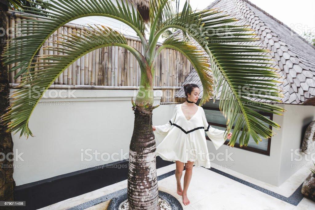 Tropikal bahçesinde bulunan palmiye ağacı ve beyaz arka plan beyaz tunik kadında. Moda çekimi özel bir Villa. Bej elbise, yalınayak royalty-free stock photo