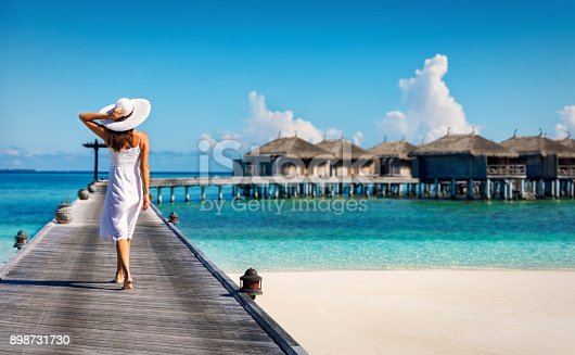 istock Woman in white walking over a wooden jetty 898731730
