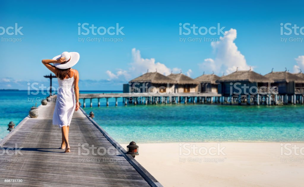 Woman in white walking over a wooden jetty stock photo