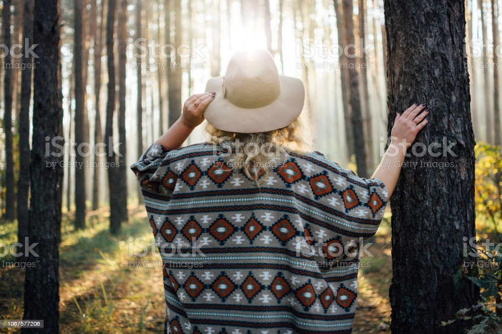 Woman in wide-brimmed felt hat and authentic poncho standing in a foggy forest stock photo