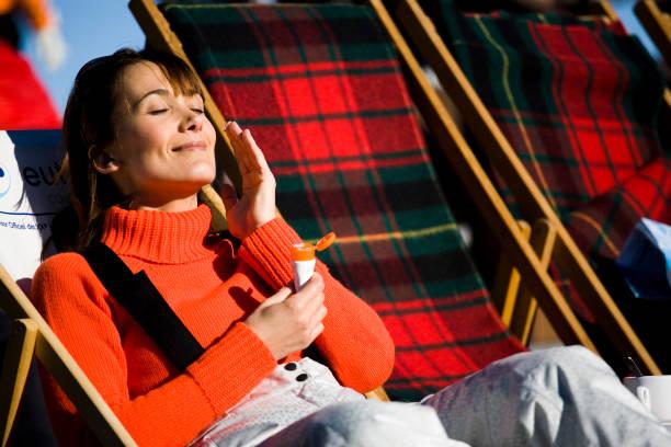 woman in winter applying solar cream stock photo