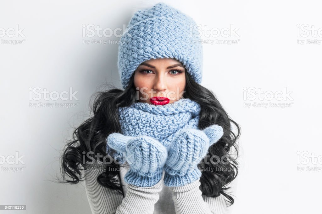 Woman in winter clothes blowing on palms stock photo