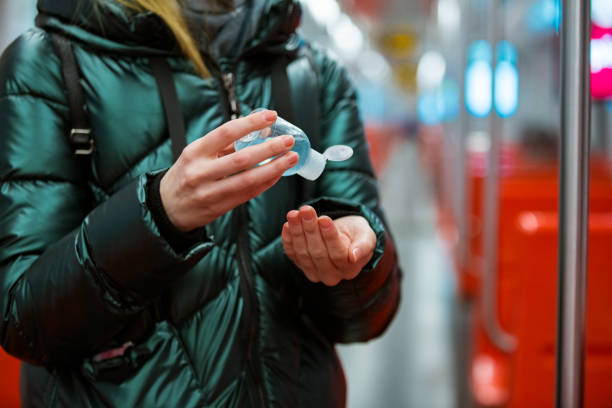 Woman in winter coat with protective mask on face standing in subway car stock photo