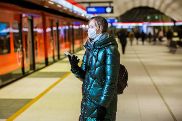 Woman in winter coat with protective mask on face standing on metro station stock photo