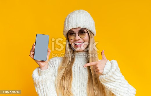 1084491176 istock photo Woman in winter hat pointing at blank smartphone screen 1187575742