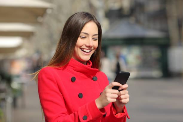 Frau im Winter Spaziergänge und nutzt Smartphone – Foto
