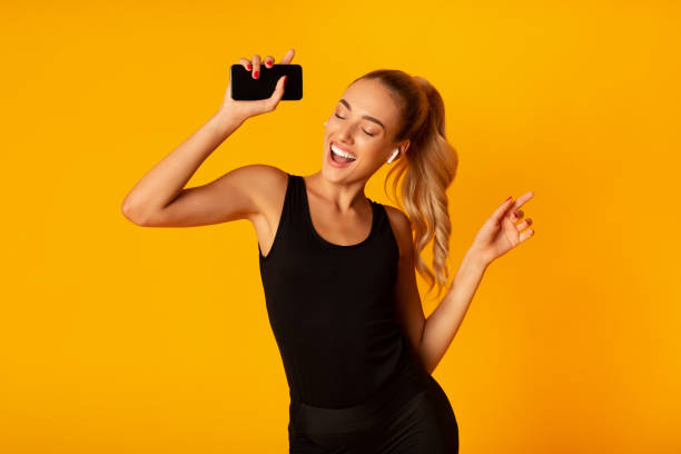 Woman In Wireless Earbuds Holding Smartphone And Dancing, Studio Shot Music App. Sporty Woman In Wireless Earbuds Holding Smartphone And Dancing Over Yellow Background. Studio Shot wireless headphones stock pictures, royalty-free photos & images