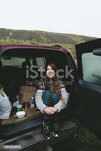 Happy woman waiting for breakfast after sleeping in the car in Iceland