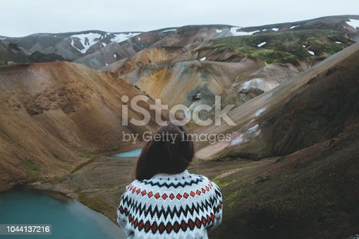 Woman sits on the top and looks at colorful mountains and lake in Iceland Highlands